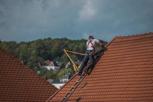 couvreur professionnel montant sur un toit